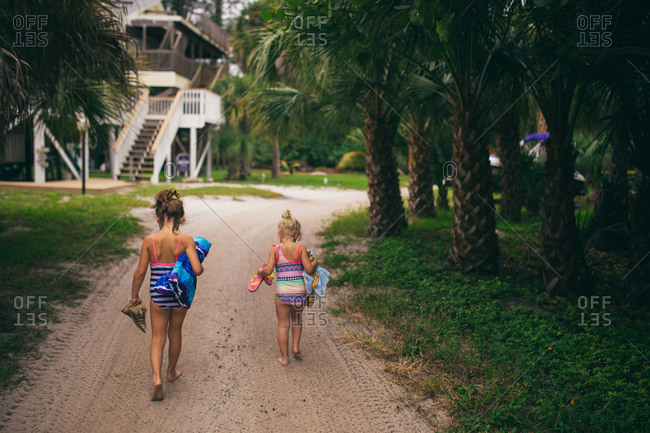 Kids walking up a sandy path in swimsuits carrying beach towels