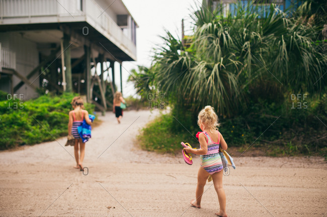 Kids walking to the beach in swimsuits carrying beach towels