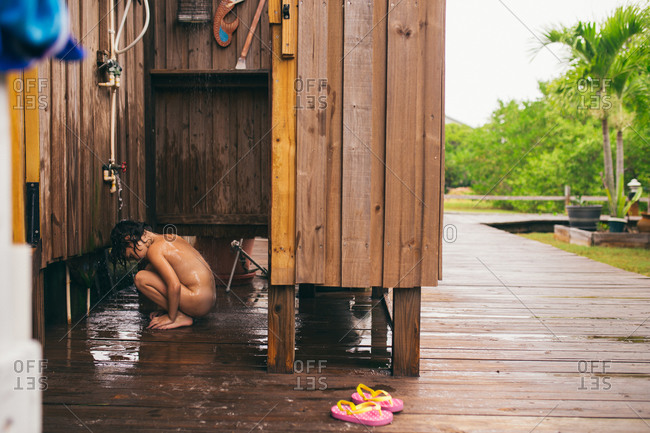 Little girl showering in an outdoor shower after swimming at the beach