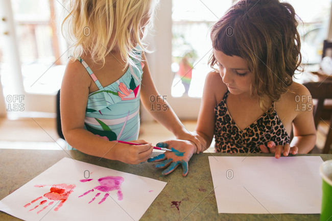 Sisters finger painting hand prints