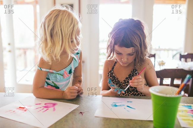 Sisters painting their hands to make prints