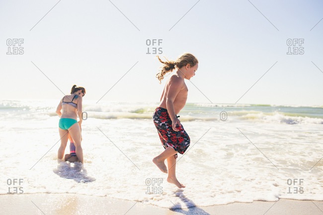 Little boy jumping in the waves on the beach