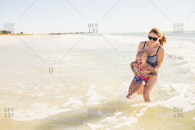 Mother swinging her daughter around in the water at the beach