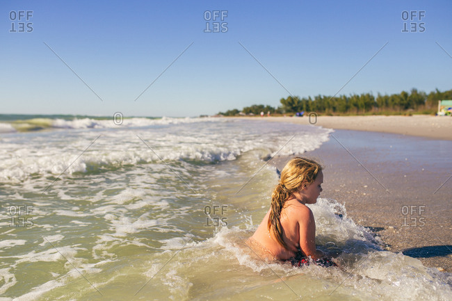 Little boy sitting in the waves on the beach