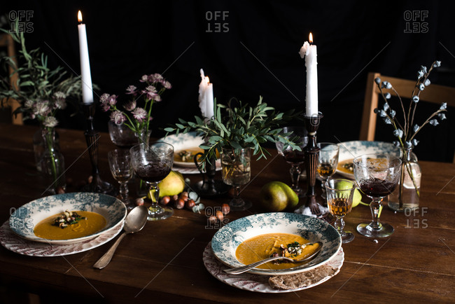 Bowls of soup and candles on a decorated wooden table