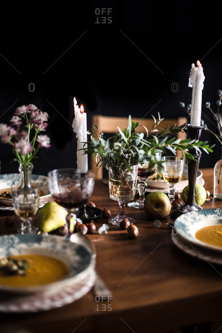 Table set with bowls of soup and candles