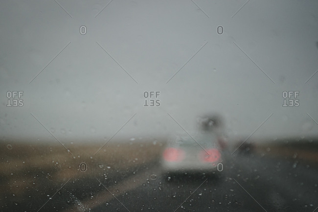 View of car ahead on road through rainy window