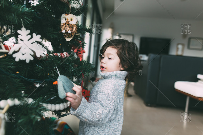 Toddler boy in turtleneck sweater checking out ornaments on his Christmas tree