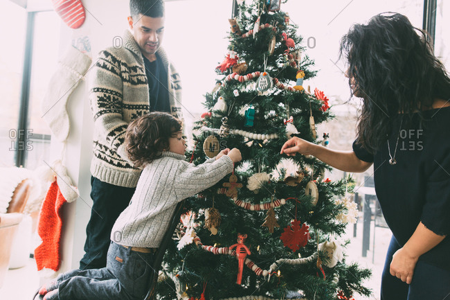 Parents and young son decorating Christmas tree