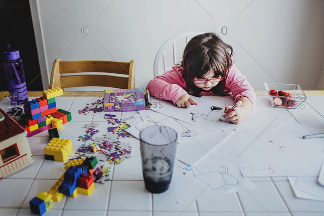 Girl drawing at table by toys