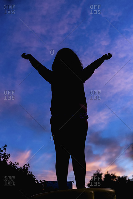 Girl silhouetted against evening sky