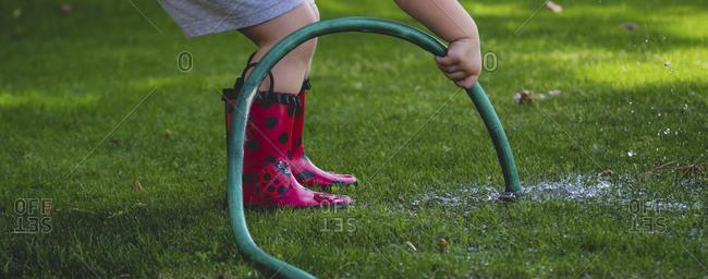 Girl holding hose against lawn