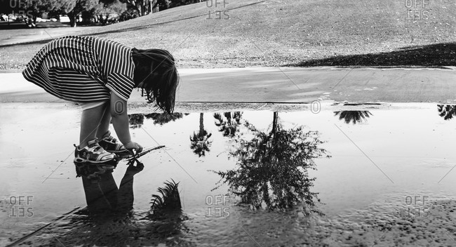 Girl picking up stick from puddle