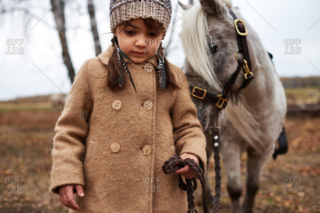 Little girl leading a miniature horse