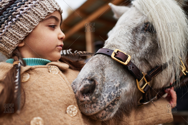 Little girl showing affection toward miniature horse