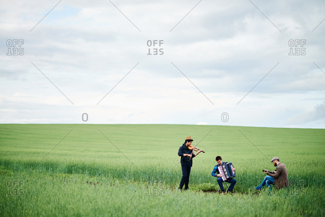 Three musicians playing in a farm field