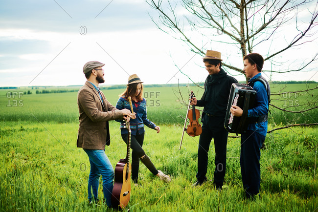 Musicians hanging out in a farm field