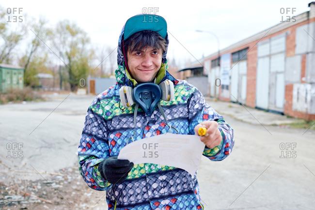 Graffiti muralist at with respirator mask