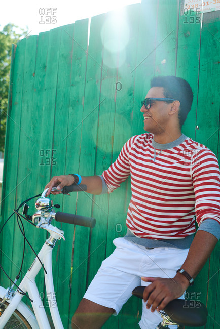 Young man against green fence with a bike