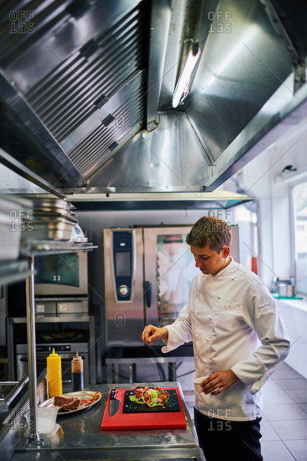 Chef plating food in a commercial kitchen