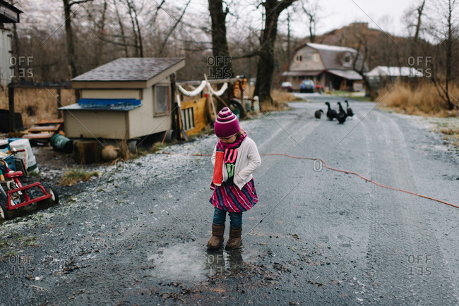 Young girl playing in muddy puddle on rural dirt road