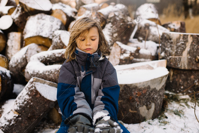 Child sitting on woodpile in the snow