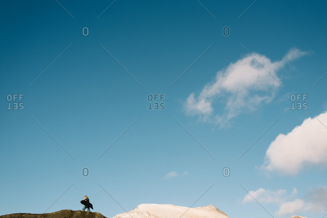 Boy on top of sand hill with sled