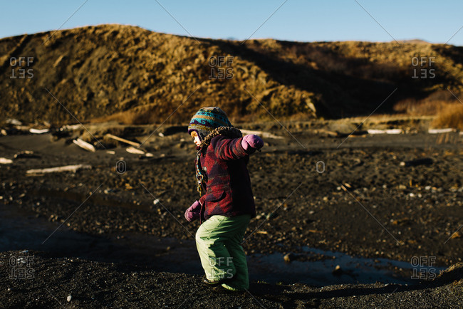 Young girl playing in muddy landscape in winter