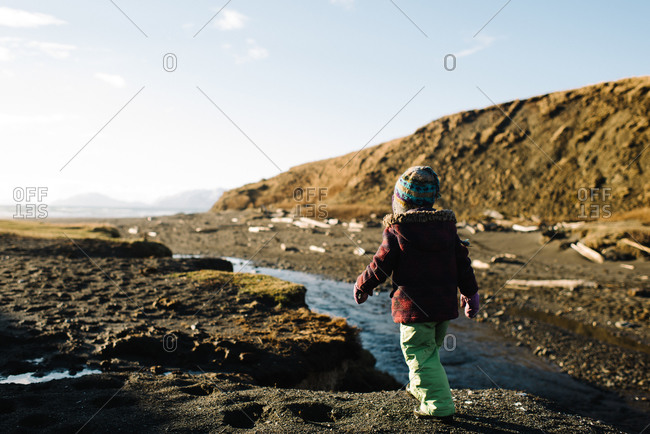 Young girl walking toward water on Alaskan coast