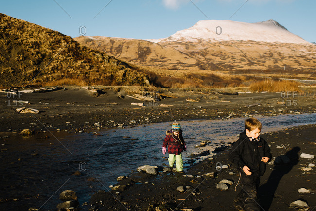 Two young children walking on bank of stream in Alaska