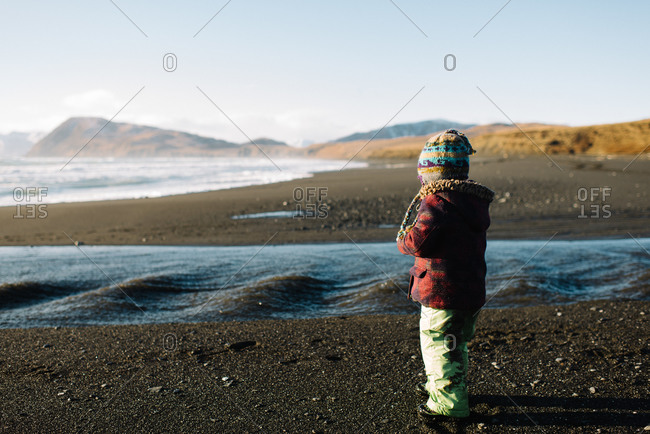 Young girl watching water flowing over beach into the sea