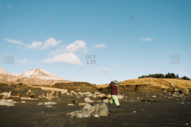 Girl in winter gear jumping off rock onto beach
