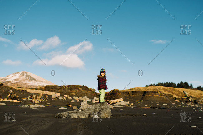 Happy young girl standing on beach rock in winter
