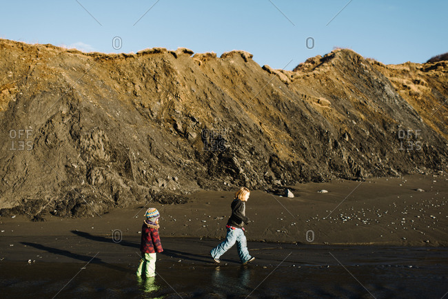 Two young children playing near runoff water on beach