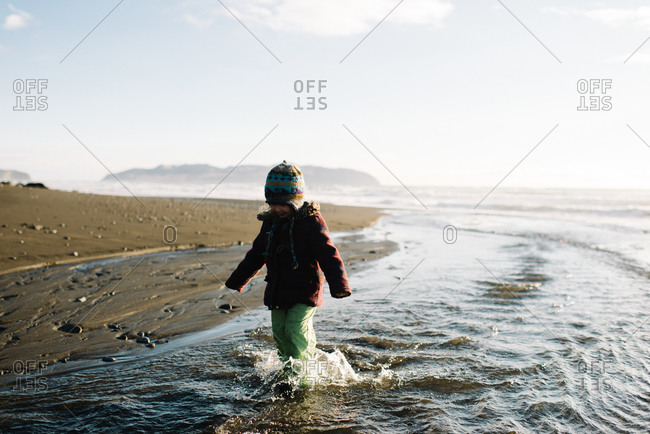 Young girl wading in stream runoff on beach