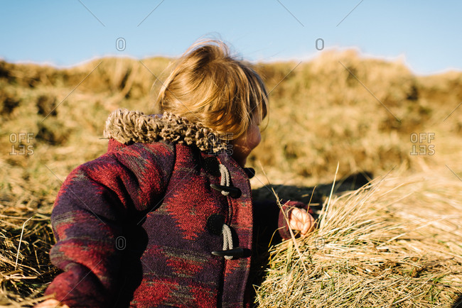 Young girl peeking over grassy hill