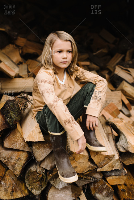 Portrait of handsome young boy sitting on a wood pile