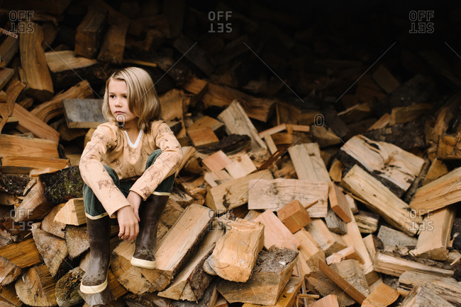 Handsome young long-haired boy sitting on wood pile