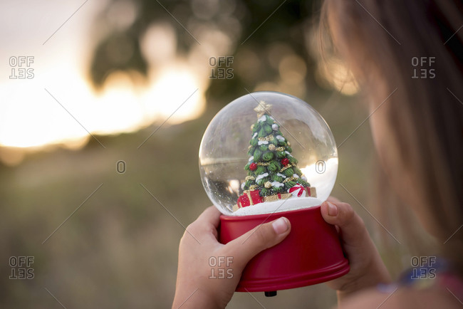 Girl holding a snow globe with a Christmas tree inside