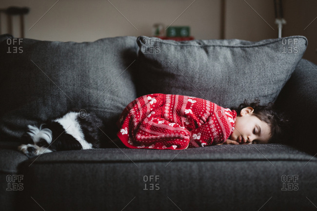 Little girl napping on the sofa by her dog