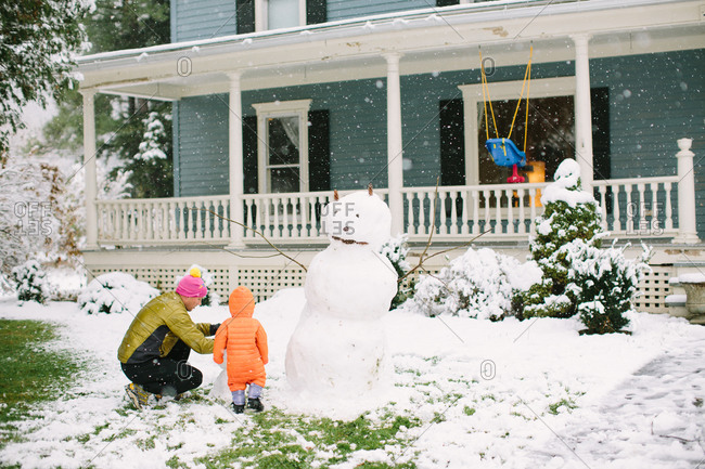 Young child building snowman with father in front yard