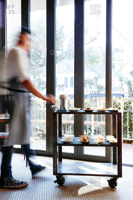 Waiter standing at a serving cart in front of large windows