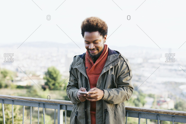 Portrait of smiling young man looking at his smartphone