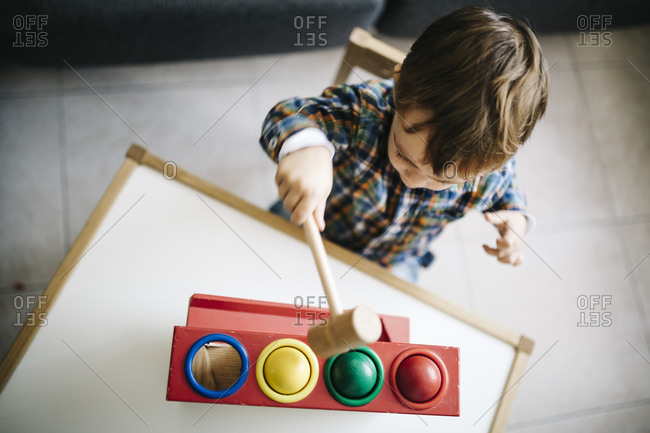 Little boy playing with wooden motor skill toy
