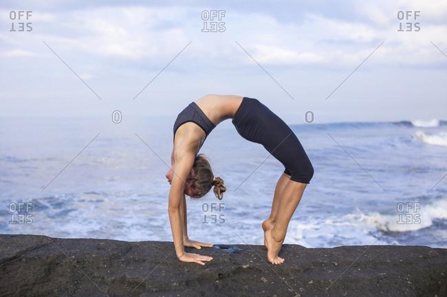 Woman practicing yoga at the coast