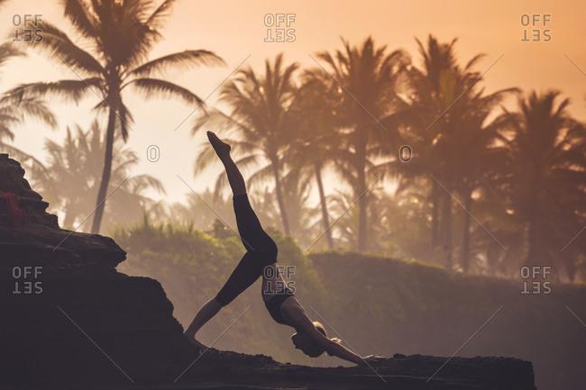 Woman practicing yoga at the coast at dusk