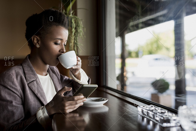 Young woman sitting in a cafe using smartphone while drinking coffee