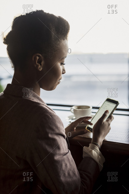 Young woman sitting in a cafe using phablet