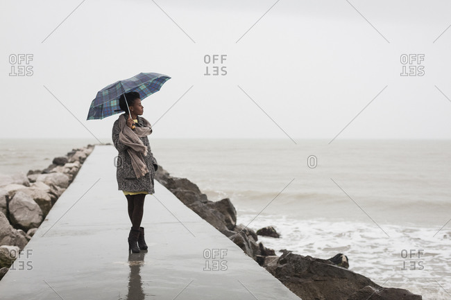 Woman with umbrella on a rainy day looking at the sea