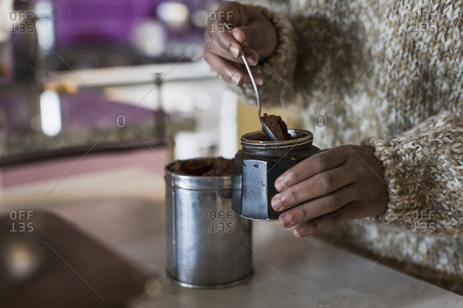 Young woman in kitchen preparing coffee